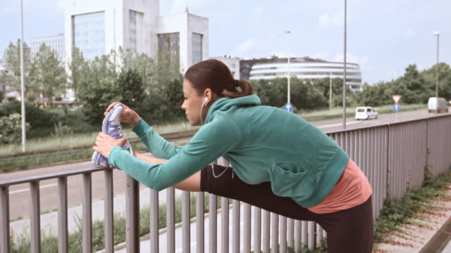 LD Female jogger stretching her legs on a fence video