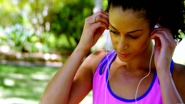 女性のジョガー女性 4 k 公園で彼女のヘッドフォンを調整 - 女性選手点の映像素材/bロール