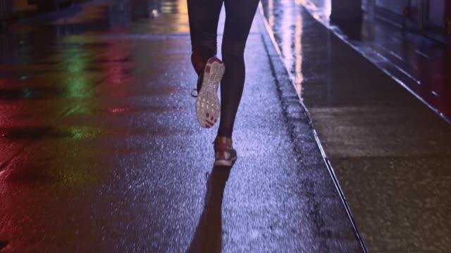 vídeos de stock, filmes e b-roll de slo mo tu ts feminino para corrida em cidade à noite - noite