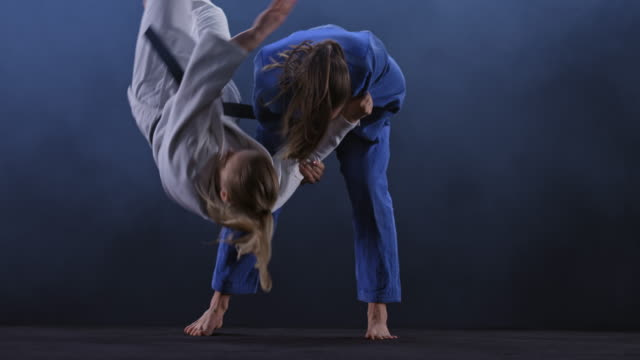 SLO MO LD Female judoka in blue outfit throwing her opponent on the floor