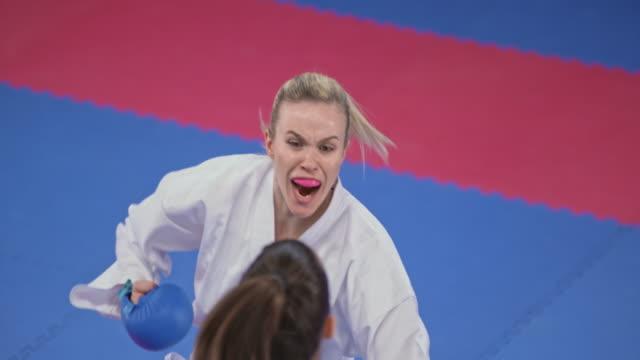 slo mo kadın karate rakip dövüş sırasında bir dişlik giyiyor - karate stok videoları ve detay görüntü çekimi