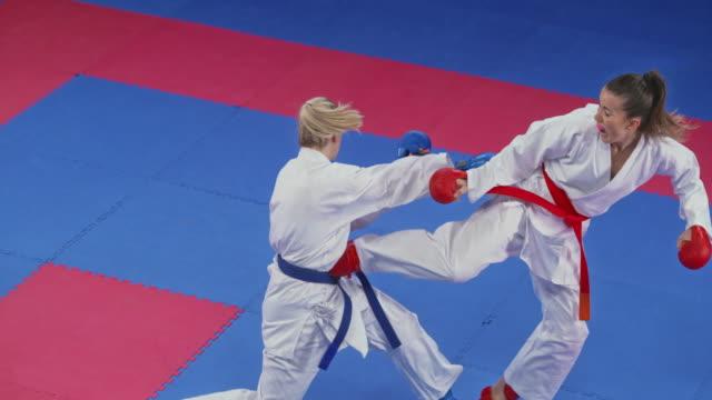 slo mo kadın karateist bir rekabette midesinde rakibin tekme - karate stok videoları ve detay görüntü çekimi