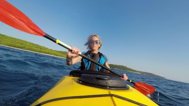 ld kayaker femmina che pagaia un kayak di mare giallo sotto il sole - donne mature video stock e b–roll