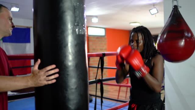 kobieta kick-boxer praktykujących z trenerem w siłowni - 30 39 lat filmów i materiałów b-roll