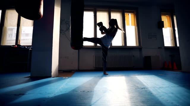 vídeos de stock e filmes b-roll de female kick-boxer training - boxe tailandês