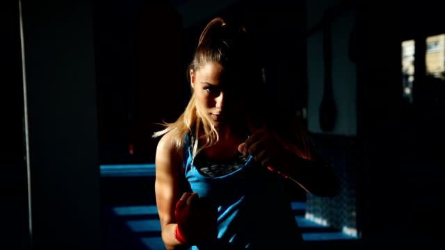 Female kick-boxer training SLOW MOTION: Young female kick-boxer is training in gym cross training stock videos & royalty-free footage
