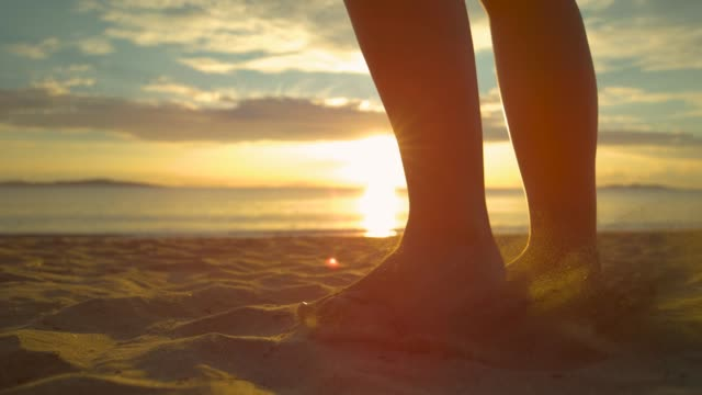 slow motion: female kicking sand sends sparkling particles flying around beach. - dito del piede video stock e b–roll