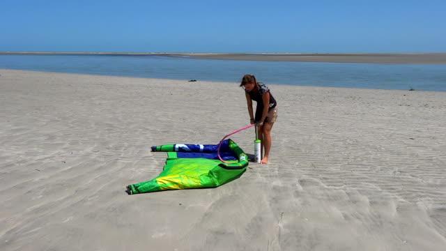 female kiteboarder inflating a kite - värmepump bildbanksvideor och videomaterial från bakom kulisserna