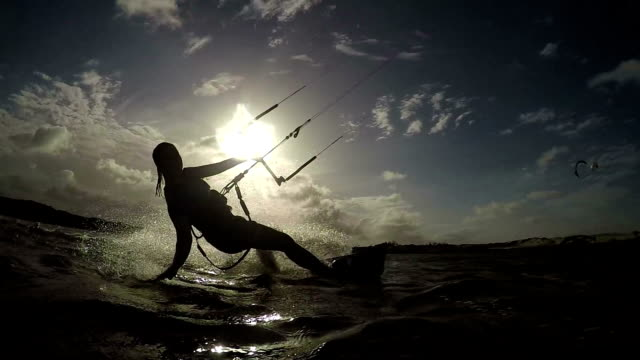 SLOW MOTION: Female kiteboarder riding and splashing water into camera video