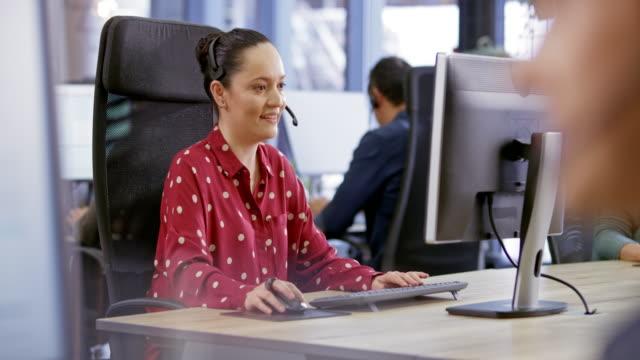 vidéos et rushes de ld femme agent de centre d'appels d'amérique latine fournissant le soutien à la clientèle à son poste de travail - relation client