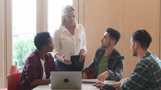Mujer profesora hablando con tres estudiante usando laptop - vídeo