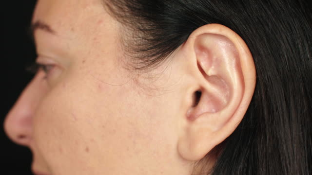 female left ear close up. ear of adult brunette woman. parts of face and body - orecchio umano video stock e b–roll