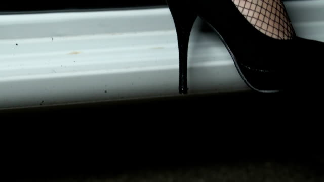 Female leg in high heels and pantyhose getting in car, party taxi services