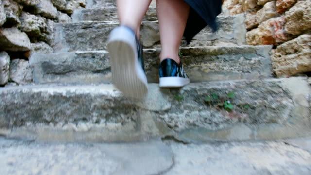 Female legs feet walking up stone steps staircase