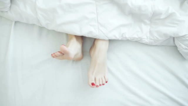 Female legs in bed view from above, white bedding, dancing
