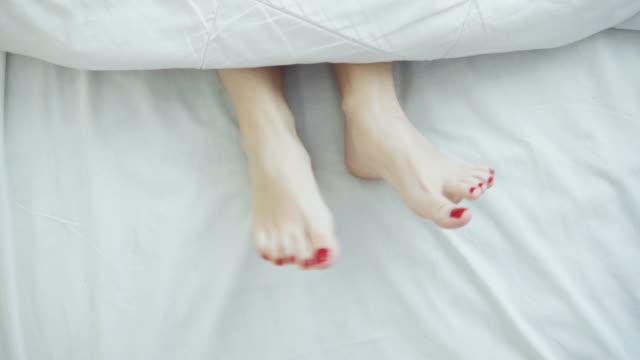 female legs in bed view from above, white bedding, dancing - kołdra filmów i materiałów b-roll