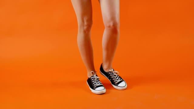 weibliche beine in schwarz-weißen turnschuhen tanzen auf hellem hintergrund im studio. klassische schuhe. gesunder lebensstil, aktive menschen. - mittelstufenlehrer stock-videos und b-roll-filmmaterial