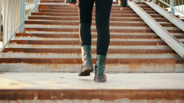 Female legs in black leather boots walking on upstairs outdoor. Rocker woman feet in heavy black boots climbing stairs on ground crossing back view.