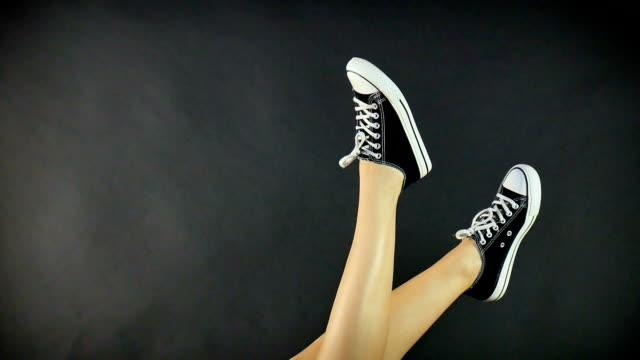 weibliche beine in klassischen schwarzen und weißen turnschuhen. die beine sind nach oben angehoben und hin und her baumeln. grauen, schwarzen hintergrund. klassische schuhe, retro-stil. gesunde lebensweise - mittelstufenlehrer stock-videos und b-roll-filmmaterial