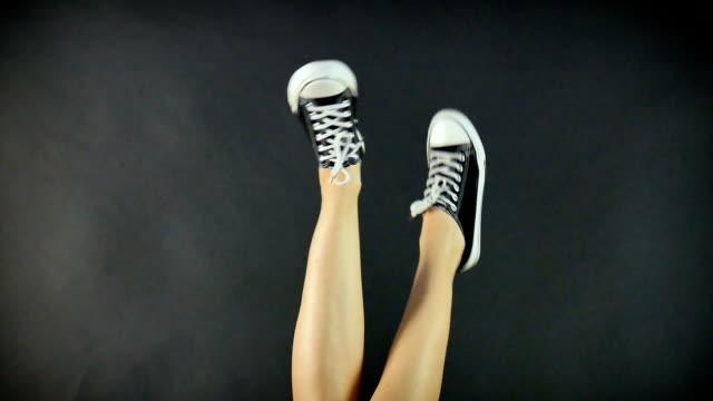 weibliche beine in klassischem schwarz-weiß turnschuhen. die beine sind nach oben angehoben und hin und her baumeln. schwarzer hintergrund. klassische schuhe. gesunde lebensweise - mittelstufenlehrer stock-videos und b-roll-filmmaterial