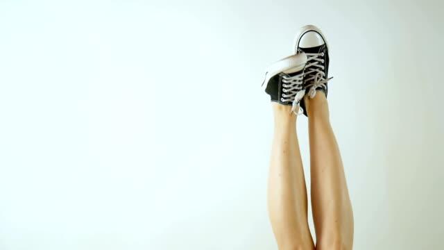 weibliche beine in klassischem schwarz-weiß turnschuhen. die beine sind nach oben angehoben und hin und her baumeln. grau hinterlegt. klassische schuhe. gesunde lebensweise - mittelstufenlehrer stock-videos und b-roll-filmmaterial