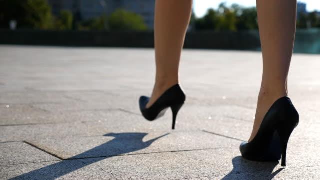 vídeos de stock, filmes e b-roll de pernas femininas em sapatos de salto alto andando na rua urbana. pés de mulher de negócios jovem em calçado de salto alto, indo na cidade. garota pisando para trabalhar. câmera lenta close-up vista de ângulo baixo - salto alto