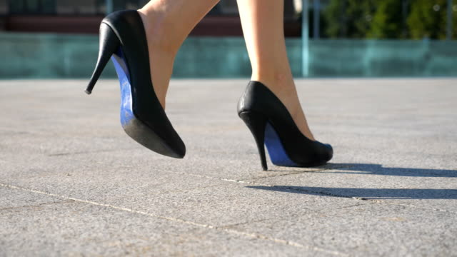 Female legs in high heels shoes walking in the urban street. Feet of young business woman in high-heeled footwear going in the city. Girl stepping to work. Slow motion Close up Low angle view