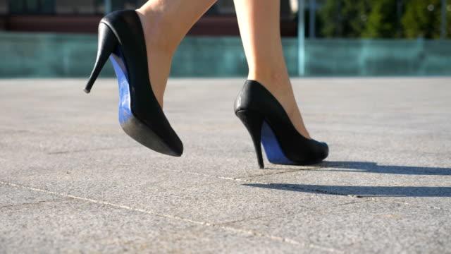 都市通りを歩いてかかとの高い靴で女性の足。都市はかかとの高い靴の若いビジネス女性の足。ステップ動作する女の子。スローモーションを低角度のビューを閉じます - 後に続く点の映像素材/bロール