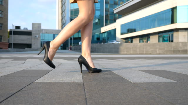 female legs in high heels shoes walking in the urban street. feet of young business woman in high-heeled footwear going in the city. girl stepping to work. slow motion close up side view - high heels stock videos & royalty-free footage