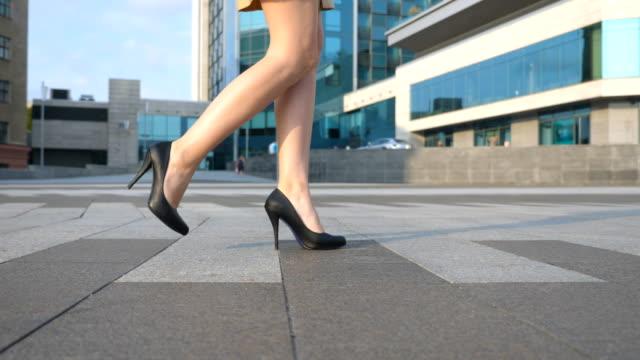 vídeos de stock, filmes e b-roll de pernas femininas em sapatos de salto alto andando na rua urbana. pés de mulher de negócios jovem em calçado de salto alto, indo na cidade. garota pisando para trabalhar. câmera lenta close-up vista lateral - salto alto