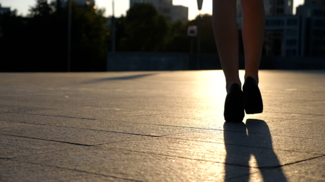 female legs in high heels shoes walking in the urban street with sun flare at background. feet of young business woman in high-heeled footwear going in the city. girl stepping to work. slow motion low angle view - scarpe video stock e b–roll