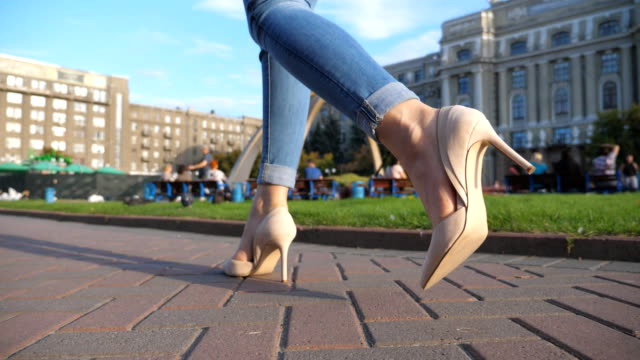 female legs in high heels shoes walking in urban street. feet of young woman in high-heeled footwear going in city. girl stepping on sidewalk. low angel view slow motion close up - scarpe video stock e b–roll