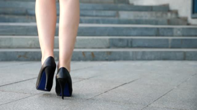 vídeos de stock, filmes e b-roll de pernas femininas em sapatos de salto alto andando nas escadas. pés de empresária, intensificando-se na escada. mulher elegante subindo a escada. jovem garota pisar na rua da cidade. close-up vista de baixo ângulo de câmera lenta - salto alto