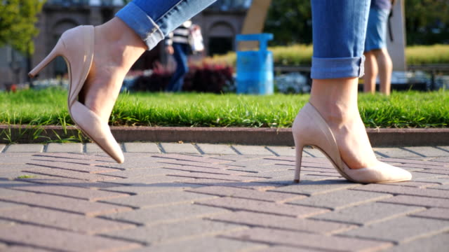 female legs in high heels shoes walking through urban street. feet of young woman in high-heeled footwear going in city. unrecognizable girl stepping at sidewalk. side view slow motion close up - fare un passo video stock e b–roll