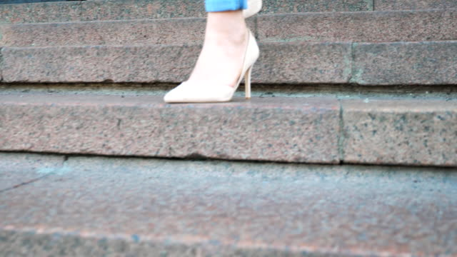 ジーンズとトレンディなハイヒールシューズの女性の足が階段を下りる。階段を踏む魅力的な女の子のスリムな足。階段で降りる若い女性。街の通りを歩いている女の子。スローモーション - 階段点の映像素材/bロール