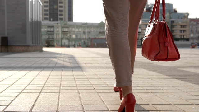 Female legs in red high-heeled shoes walks around the modern city - vídeo