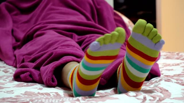 kvinnliga ben i strumpor med tår avkopplande i sängen - strumpa bildbanksvideor och videomaterial från bakom kulisserna