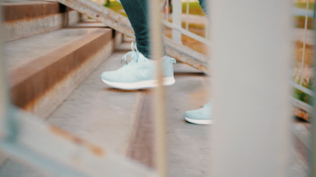 Female legs in sport sneakers and blue jeans walking on upstairs outdoor. Woman feet in sport shoes climbing stairs on ground crossing.