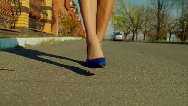 female legs in stiletto shoes walking on street - fare un passo video stock e b–roll
