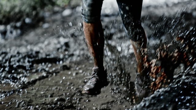 SLO MO DS Female legs running across a muddy puddle at night