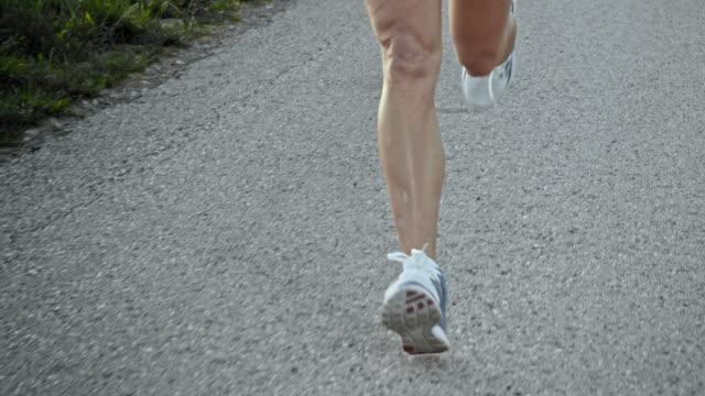 SLO MO TS Female legs running on asphalt video