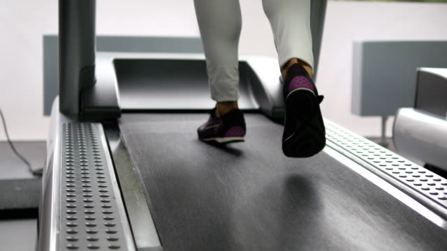 Female legs walking and running on treadmill in gym. Young woman exercising during cardio workout. Feet of girls in sport shoes training indoor at sport club. People jogging. Close up video