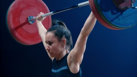 SLO MO TU Female lifter doing the snatch Medium slow motion tilt up shot of a female weightlifter performing the snatch lift at a competition. Shot in Slovenia. endurance stock videos & royalty-free footage