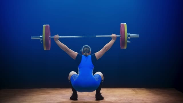 Female lifter lifting the barbell at a competition