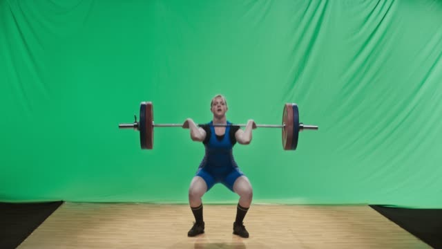 LD Female lifter lifting the barbell performing the clean and jerk lift
