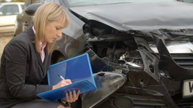 kvinnliga förlust justeraren skriva rapport om skadad bil - försäkring bildbanksvideor och videomaterial från bakom kulisserna