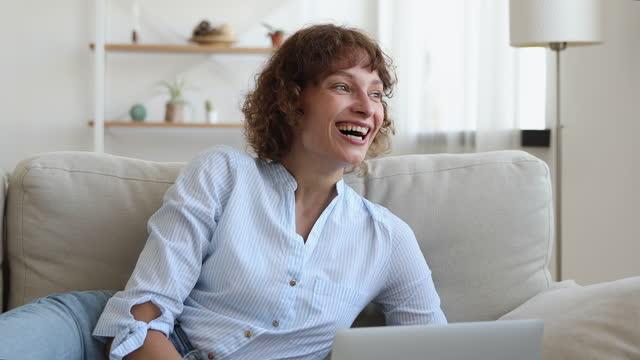 vídeos de stock, filmes e b-roll de mulher deitada no sofá usar laptop ler notícias se sente feliz - plano médio
