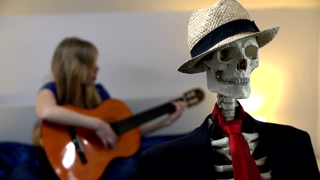 Female makes romantic atmosphere with singing and guitar Woman plays the acoustic guitar and sings songs to entertain the sitting skeleton animal skeleton stock videos & royalty-free footage