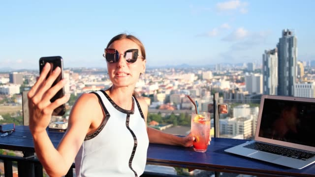 female makes selfie in a cafe on the roof of a skyscraper. girl sitting with a laptop and an orange cocktail on against the panoramic view - influencer filmów i materiałów b-roll