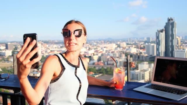 여성은 고층 빌딩의 지붕에 카페에서 셀카를 만든다. 탁 트인 전망에 노트북과 오렌지 칵테일과 함께 앉아 소녀 - influencer 스톡 비디오 및 b-롤 화면